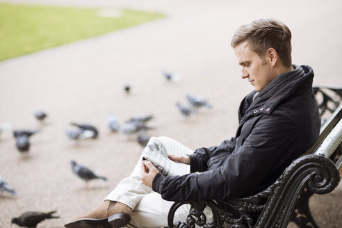 Young man sitting on park bench reading newspaper - CUF30782