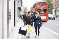 Young couple with shopping bags strolling, London, England, UK - CUF30788