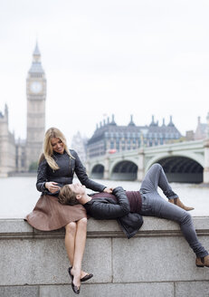 Romantic young couple on wall in front of Big Ben, London, England, UK - CUF30791