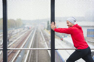 Young man doing physical training on city footbridge - CUF30794