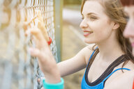 Young women standing beside fence - CUF30869