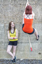 Young women climbing over wall with rope - CUF30878