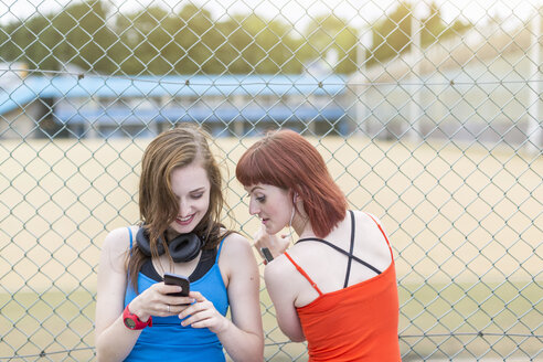 Young women using smartphone beside fence, London, UK - CUF30881