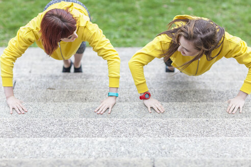 Young women doing push-ups on steps - CUF30890