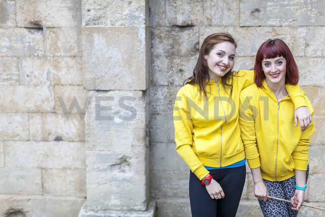 Young women smiling, stone wall in background - CUF30893 - dotdotred/Westend61