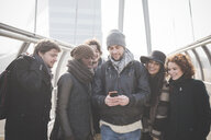 Six young adult friends on footbridge reading smartphone text - CUF31157