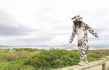 Girl wearing animal onesie balancing on wooden fence, Thingvellir, Iceland - CUF31178