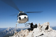 Helicopter dropping BASE jumpers on mountain, Dolomites, Italy - CUF31199