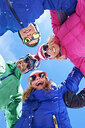 Low angle view of family in winter clothing and sunglasses - CUF31271