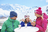 Couple having coffee with daughter, Chamonix, France - CUF31277