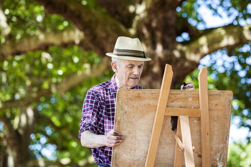 Senior man drawing in park, Hackney, London - CUF31283