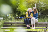 Senior woman and daughter chatting and holding hands on park bench - CUF31328