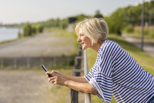 Smiling senior woman with cell phone leaning on railing at riverbank - FMKF05146