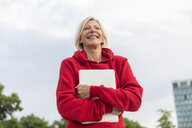 Happy senior woman wearing red hoodie holding laptop outdoors - FMKF05149