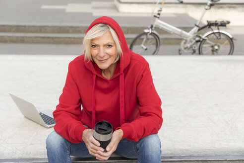 Senior woman wearing red hoodie sitting outdoors with laptop and takeaway coffee - FMKF05152