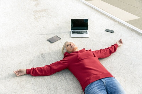 Senior woman wearing red hoodie lying on the ground next to mobile devices - FMKF05155