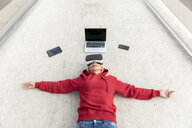 Senior woman lying on the ground wearing VR glasses next to mobile devices - FMKF05158