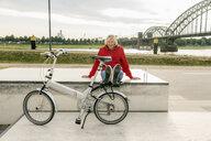 Smiling senior woman with city bike having a break - FMKF05167