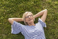 Portrait of smiling senior woman lying in grass - FMKF05170