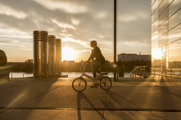Senior woman riding city bike at the riverside at sunset - FMKF05176