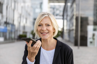 Portrait of smiling senior businesswoman using cell phone outdoors - FMKF05188