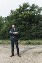 Businessman standing in remote landscape - UUF14077