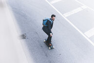 Businessman riding skateboard on the street - UUF14086