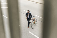 Businessman with bicycle and cell phone walking on the street - UUF14095