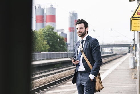Businessman with cell phone waiting at the platform - UUF14101