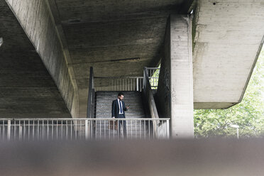 Businessman at underpass checking cell phone - UUF14119
