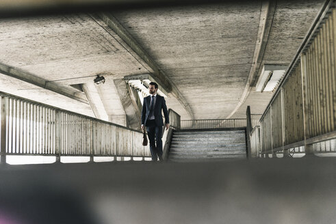 Businessman walking at underpass - UUF14122