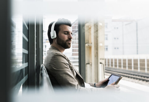 Young man with closed eyes wearing headphones and holding tablet at the station platform - UUF14143