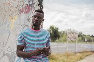 Young man in skatepark leaning against graffiti wall, listening music - ACPF00011