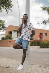 Young man in the city, standing in the street, talking on the phone - ACPF00020