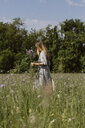 Italy, Veneto, Young woman plucking flowers and herbs in field - ALBF00407