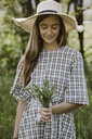Italy, Veneto, Young woman holding bunch of tarragon - ALBF00419