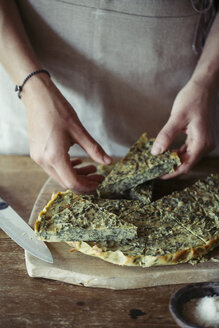 Young woman garnishing homemade chickpea and herb cake - ALBF00428