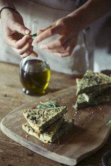 Young woman garnishing homemade chickpea and herb cake - ALBF00431