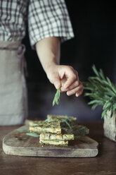 Young woman garnishing homemade chickpea and herb cake - ALBF00437