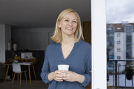 Smiling woman holding cup of coffee looking out of balcony door - RBF06299