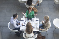 High angle view of businessmen and businesswomen having lunch meeting on hotel terrace - ISF09713