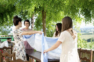 Group of female friends, laying tablecloth on table, outdoors - CUF31486