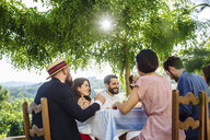 Group of friends having meal together, outdoors, rear view - CUF31492