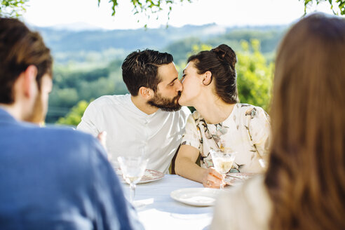 Group of friends having meal together, couple kissing, outdoors - CUF31495