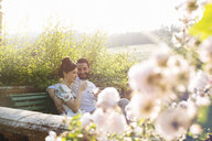 Mid adult couple sitting on bench, outdoors, drinking champagne - CUF31498