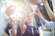 Group of friends, drinking champagne, making toast, outdoors, low angle view - CUF31504