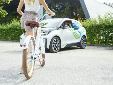 Woman with bicycle in front of electric car - CVF00799
