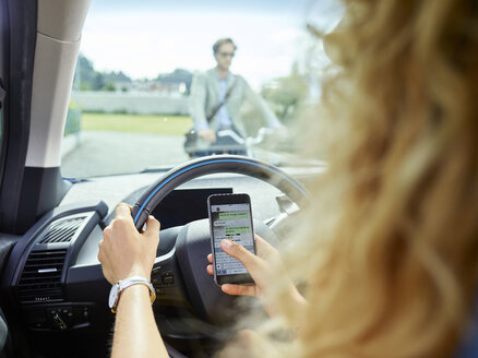 Young woman in electric car texting on cell phone - CVF00802