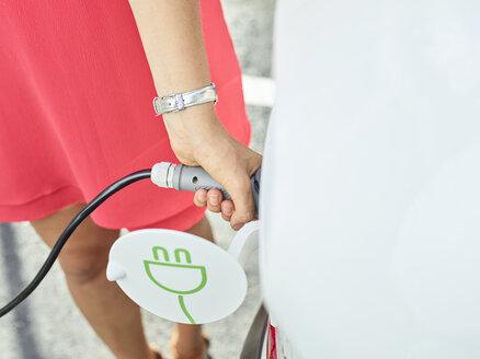 Close-up of woman charging electric car - CVF00811