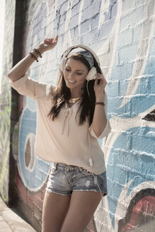 Young woman outdoors, listening to music through headphones, dancing - CUF31544
